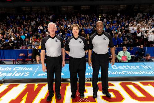 Three Basketball Officials standing on the court